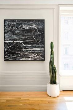 Framed paint splatter artwork with cacti for home decor.