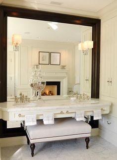 framed mirror, antique bench, framed etchings, beautiful sinks, fireplace, bathroom