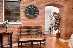 View from living room into foyer in a downtown condo. Includes exposed brick with arched doorway and oak hardwood floors.
