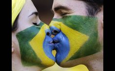 Com os rostos pintados formando, juntos, a bandeira do Brasil, casal se beija em Belo Horizonte
