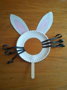 Adorable Easter Bunny Mask...*Paper Plate With Center Cut Out, *White Construction Paper Cut Into 2 Bunny Ear Shapes, *Pencil To Draw Inner Shape Of Bunny Ear, *Pink Crayon To Color The Inner Ear, *Black Construction Paper Cut Into Strips As Shown For Whiskers, *Popsicle Or Tongue Depressor Stick & *Elmer's Glue (Or Hot Glue With Adult Supervision)...Click On Picture For This & Other Bunny Mask Ideas...