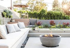Sunken patio is filled with a concrete bench lined with white outdoor cushions and gray striped outdoor pillows faces a concrete bowl fire pit surrounded by black river rocks. Concrete Patios, Concrete Fire Pits, Concrete Bowl, Concrete Bench, White Concrete, Sunken Fire Pits, Fire Pit Backyard, Backyard Patio, Backyard Landscaping
