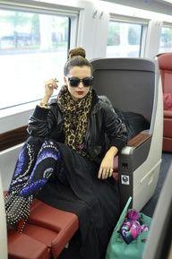 Aureta wearing printed Alexander McQueen Pants, Comme des Garcons black dress, Gucci leather jacket, Louis Vuitton leopard scarf, Hermes turquoise Birkin bag, and Louboutin black studded booties