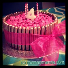 Very easy birthday cake! Victoria sponge, chocolate fudge icing, chocolate fingers and pink smarties. Added an edible pink sparkle spray onto the chocolate fingers and a pink ribbon to finish. There's also a surprise inside!