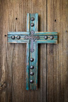 A reclaimed pine wood cross with hand hammered metal clavos and finished with a metal cross at the center. A wonderful piece. - Handmade cross - Reclaimed pine wood - Antiqued turquoise and brown pati