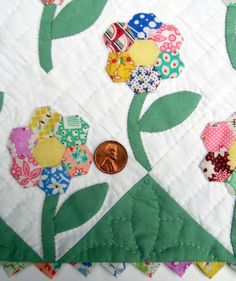 Mini Hexi Flowers - I love how she used vintage fabrics.  This is a perfect project for my feedsack collection!  (Perhaps use two leaves for each flowers.)