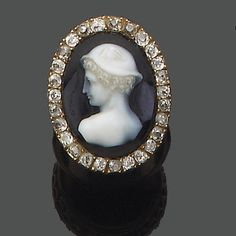 A late 19th century hardstone cameo and diamond ring, 1880 ~ The oval onyx plaque carved to depict the head and shoulders of Mercury within an old brilliant-cut diamond border,