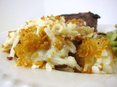 Creamy Potato Casserole  1 (28-32oz) bag frozen shredded hash brown potatoes 1 can cream of chicken soup 1 can cream of mushroom soup 16 oz sour cream 1 tsp pepper 1/2 cup butter, melted 2 cups corn flakes, crushed 1/4 cup butter, cubed