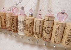 Wine cork jewelry holder.  These get more compliments from people.... some even call us genius!  We like that!!!  Wine corks are attached to pieces of wine crates then hooks & beads are added for fun & flair.  You can even hang earrings from the chain.  The ultimate in up-cycling!