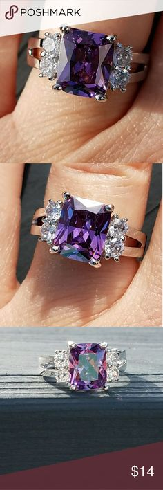 New 18k gold plated purple cubic zirconia ring This is a brand new 18 karat gold plated ring. The main stone is a rectangle purple cubic zirconia. It has 2 small round clear cubic zirconia stones on each side of the purple stone. Jewelry Rings
