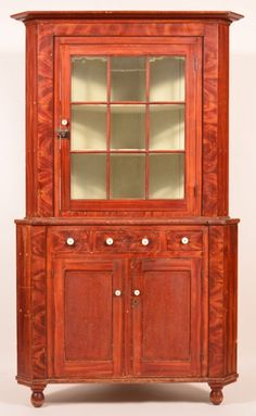 "Sold $8,000 York County, Pennsylvania Grain Paint York County, Pennsylvania Grain Paint Decorated Softwood Two-Part Corner Cupboard attributed to John Rupp, (1809-1899) Hanover, PA. Bold grain painted decoration, stepped cornice with single nine pane glazed upper door, above three split dovetailed drawers, two lower sunken paneled doors, molded base with turned feet. 84""h. x 50""w. x 25""d. Condition: good with normal wear."