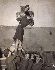 Actress Marlene Dietrich is hoisted up to kiss her loved one, as he arrives home from Worl War II. New York, 1945.