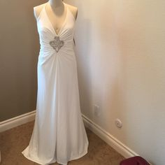 Jessica McClintock white gown. This beautiful gown has a halter design, beaded rhinestone front brooch and slight tail. Perfect for that special occasion. Dress size labeled as 12. Jessica McClintock Dresses