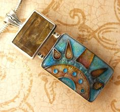 This cloisonne enamel pendant is a striking blend of pale aqua, gold and tan with subtle shading of rose pink. It was created by firing multiple