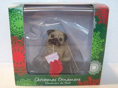 One Sandicast Dog Ornament for Hanging on the Christmas Tree.  Pug, Fawn Color, Item XSO12204, UPC 746314016725 wearing a Christmas Stocking  Packaging states that the Dog Ornament has been Hand Cast and Hand Painted.