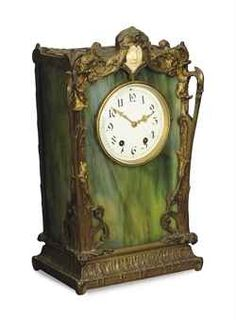 AN ART NOUVEAU GILT-BRONZE-MOUNTED SLAG GLASS AND IVORY-INSET MANTEL CLOCK,