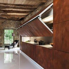 #mulpix Cozinhas ocultas podem trazer um clima de surpresa ao décor. Esta da foto, criada pela marca alemã Warendorf, fica escondida atrás de um belo painel de madeira, com vistas para um living integrado. Prático e elegante!  #decoração  #architecture  #design  #reforma  #retrofit  #arkpad  #decor