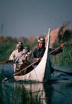 Marsh Arab men steer a tarada, or canoe, through the waters of the Marshes of Iraq. | Location: The Marshes, near Nasiriya, Iraq. 1974