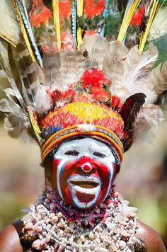 Colorful woman in Papua New Guinea wearing shell necklaces and a feather headdress.