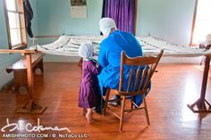 3444 a young girl stands at her mothers knee as she works on a quilt