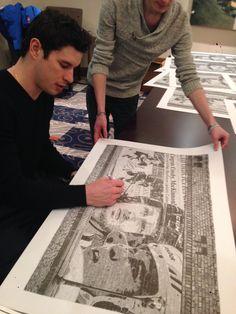 Pittsburgh Penguin star Sidney Crosby, signing Robb Scott's art prints.