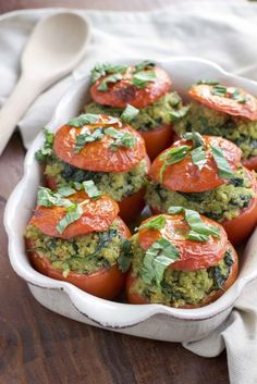 Roasted stuffed tomatoes that are filled to the brim with a flavorful mixture of pesto quinoa and fresh spinach. Vegan, dairy-free, and gluten-free.