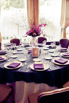 Purple tablecloth and white plates with menus and a single, tall floral centerpiece.