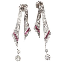 A pair of white gold, ruby and diamond pendant earrings of openworked pierced design, set throughout with brilliant-cut diamonds and a line of rubies, total diamond weight of approximately 1.30 carats.