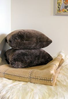 Glorious soft grizzly brown shearling pillows on border stitched caramel hide carpet on angora goat throw.