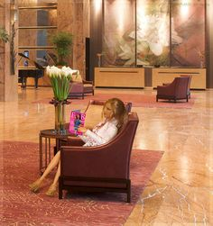 "The Reader. In this photo: Barbie® Basics Model No. 12 Collection 001 re-bodied on an articulated Fashionistas™ body. She's reading this month's issue of ""FAB"" at a hotel lobby."