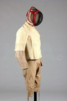 A rare fencing ensemble, French, late 18th century to early 19th century, comprising padded natural linen jacket with chamois breast and upper right arm, bone buttons down one side, stand collar, the tan calico breeches with similarly buttoned small fall, the wire mesh helmet (circa 19th century) with red morocco bindings and head brace.