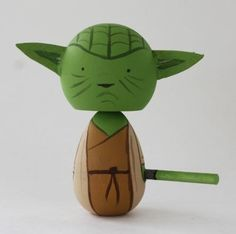 Yoda Kokeshi - Kokeshi are Japanese dolls, originally from northern Japan. They are handmade from wood, have a simple trunk and an enlarged head with a few thin, painted lines to define the face. The body has a floral design painted in red, black, and sometimes yellow, and covered with a layer of wax. One characteristic of kokeshi dolls is their lack of arms or legs. The bottom is marked with the signature of the artist.