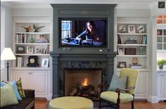 This is a great example of a dark fireplace mantel with white built ins on the side. It's a great juxtaposition between the traditional and modern.