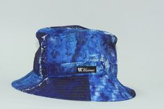 The Waimea Blue Corrosion Bucket Hat. The Blue Corrosion Bucket by Waimea- This all-over print bucket sports trippy deep blues with splashes of white similar to that of a turbulent ocean. You know you'd look good with it!
