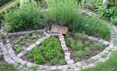 Petersilie, Schnittlauch und weitere Kräuter schmücken dieses ebenerdigeKräuterrad. Es wurde mitPflastersteinen aus Granit gestaltet