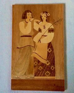 Peasant Wedding Folk Art Plaque Russian Wood Inlay Handmade 1970s  This is a special piece.  Completely charming mixed wood picture of a bride and groom dressed in simple, beautifully detailed clothing. The groom plays a song on his flute for his bride-to-be, who carries a long stem of leaves.  The plaque has a glossy lacquer finish to the face and around the edges. It is in wonderful vintage condition. There is a small area to the bottom right where a bit of lacquer was dripped, but this is…