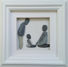 An original pebble art picture from Cornish Pebble art depicting a mother and father with their young child, all beautifully set inside a 20cm x
