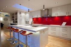 dosseret de cuisine rouge îlot central et hotte aspirante avec armoires de rangement blanches