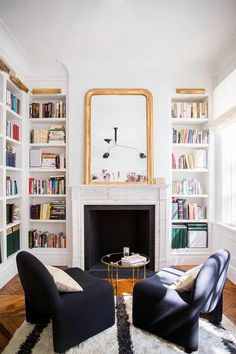 Small living room with high ceiling and floor to ceiling book cases. Gold mirror over fireplace.