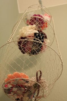 Cute idea on using a hanging fruit basket to hold hair accessories. Could work for stuffed animals too...