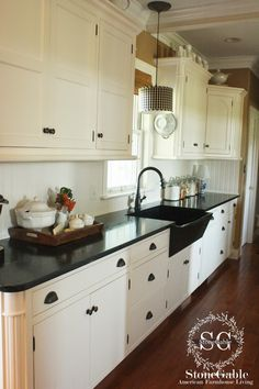 soapstone counter tops,the cabinets are white and simple, love the tray holding some goodies and the light over the farm sink.