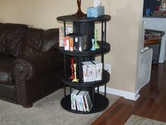 Small industrial wooden spools painted black and stacked for a three tier wooden spool shelf.