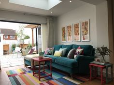 living room with teal velevet sofa and multi colour rug. Designed by interior designer Sophie Robinson for DIY SOS