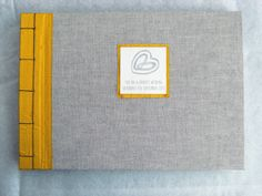 Grey Linen and Yellow Silk Wedding Guest Book.  White text paper pages.  Custom hand-printed lino cut label, mounted on matching silk.  Oriental stab-stitch binding in deep blue linen thread.