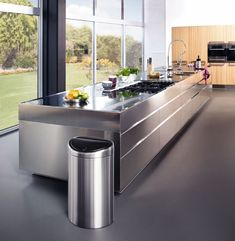 We love this kitchen and the views of the garden. Sleek and minimalist #design. Brabantia bin