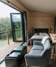 Inside the Mt Hood View Tiny House is an electric fireplace, living room area with couch and chairs positioned to take advantage of the beautiful view, and a queen size bed.