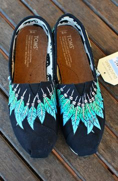 This pair of native american indian style moccasin toms shoes feature light blue and green feathers hanging around the rim of the shoe in a moccasin