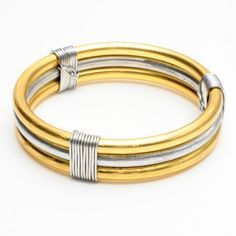 Stacked, recycled gold-and-silver tone aluminum bangles, bound with silver-tone wire by Jill Fagin