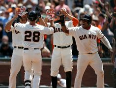 San Francisco Giants' Buster Posey (28) is welcomed to home plate by San Francisco Giants starting pitcher Madison Bumgarner (40), San Francisco Giants' Hunter Pence (8) and San Francisco Giants' Pablo Sandoval (48) after Posey hit a grand slam against the Arizona Diamondbacks ...