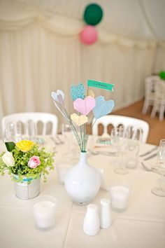 paint a jones soda bottle for the vase and then glue origami to sticks for the centerpieces.